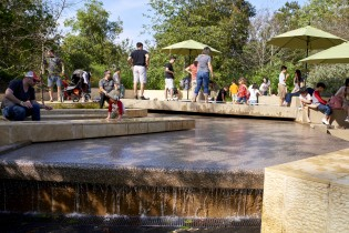 people in urban waterfall in nature gardens