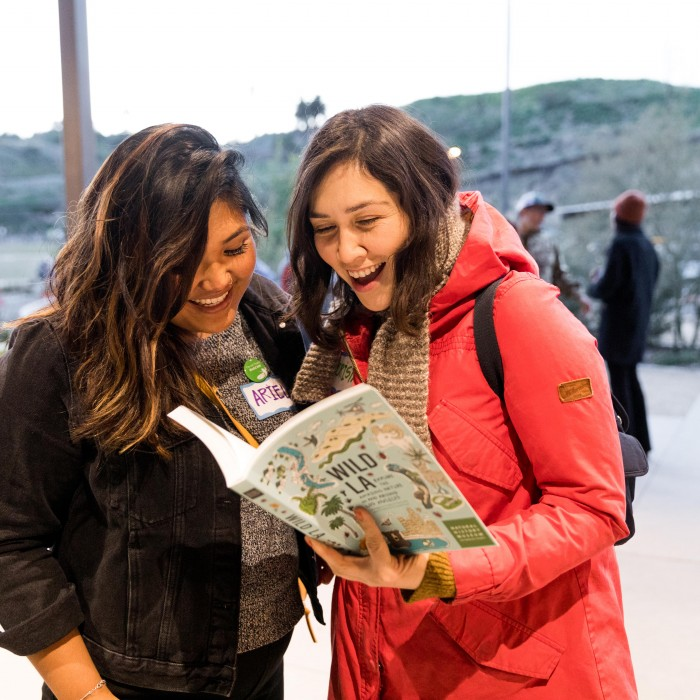 two women reading Wild LA book at community science super project party