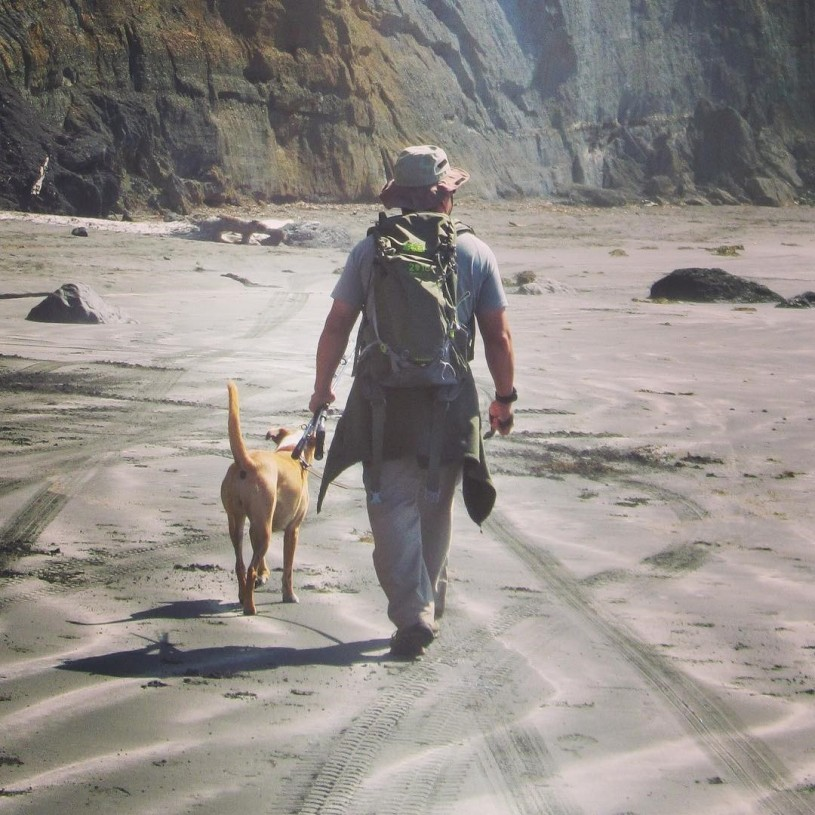 Dennis and his dog hiking on a dog-friendly beach.