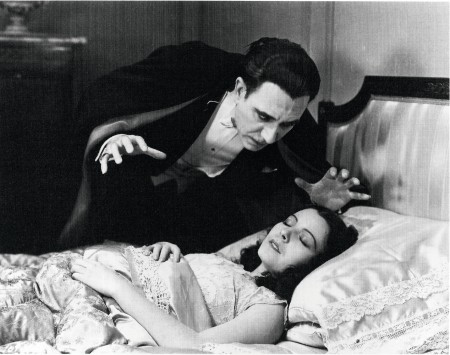 Still image from horror film Dracula. The vampire leans ominously over a sleeping woman.